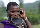 Suri woman with lip plate and mobile phone on July 5 2010 in Turgit village Omo Valley Ethiopia Piercing and lip plates are a strong part of the Suri...