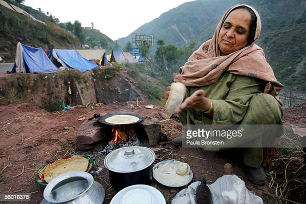 Suriah Fatmah makes roti over a fire by her roadside tent near her destroyed home October 26 2005 in Muzaffarabad Pakistan controlled Kashmir The...