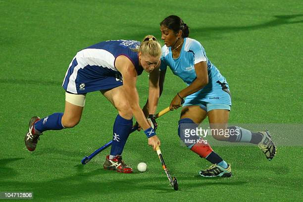 Surinder Kaur of India competes for the ball with Louise Baxter of Scotland during the women's hockey preliminary match between India and Scotland at...