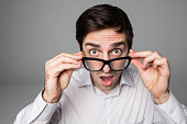 surprise entrepreneur holding his eyeglasses grey background