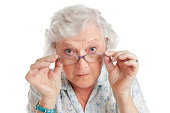 Happy surprised old senior lady looking through her eyeglasses isolated on white background.