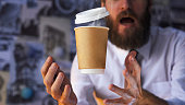 Barista, a bearded young man with open mouth in a white shirt with a tie trying to catch a paper cup with hot coffee. Background for advertising. Empty place to your logo placement
