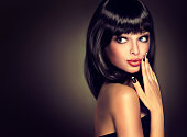 Surprised beautiful girl look aside . Model brunette with hairstyle of the care. Black hair and a black manicure on the nails.Luxury fashion style, nails manicure, cosmetics ,make-up