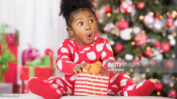 Surprised Black girl holding teddy bear toy on Christmas
