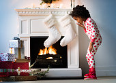 Surprised Black girl in pajamas looking down at Christmas gifts