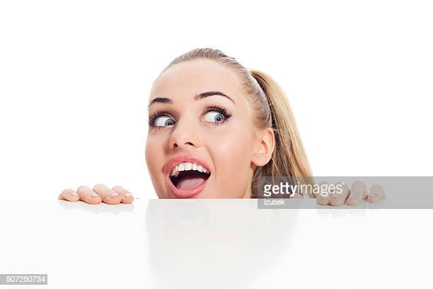 Surprised blonde young woman looking over table