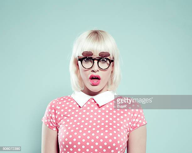 Surprised blonde young woman wearing polka dotted dress and sunglasses