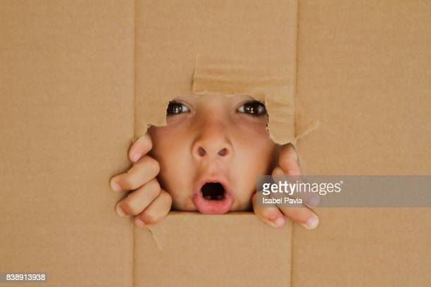 Surprised Boy looking through a hole on cardboard