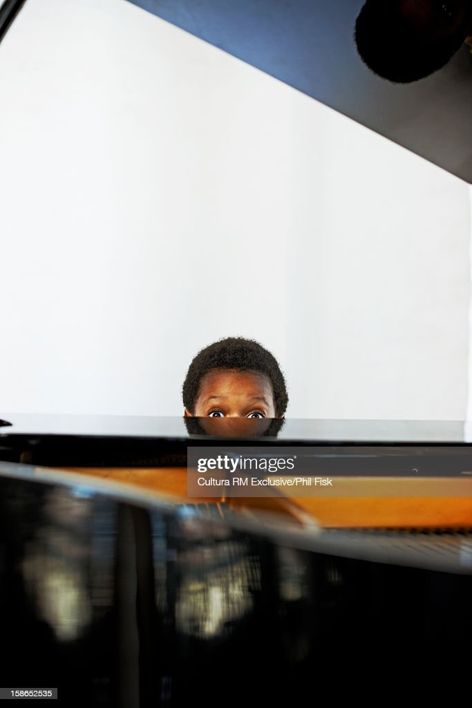 Surprised boy sitting at piano : Stock Photo