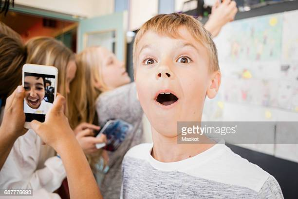 Surprised boy standing amidst friends taking selfie in corridor