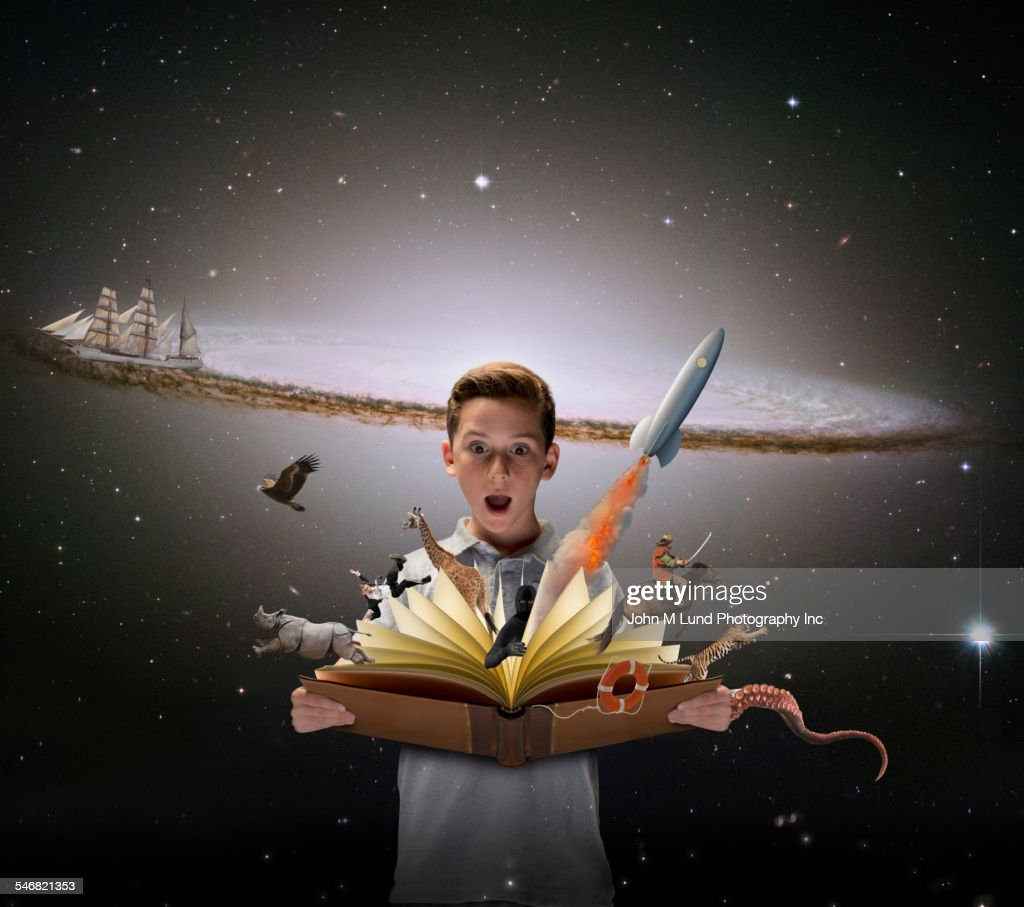 Surprised boy watching colorful characters fly out of open book : Stock Photo
