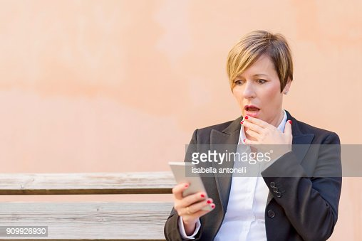 Surprised business woman calling by phone outdoor : Stock Photo