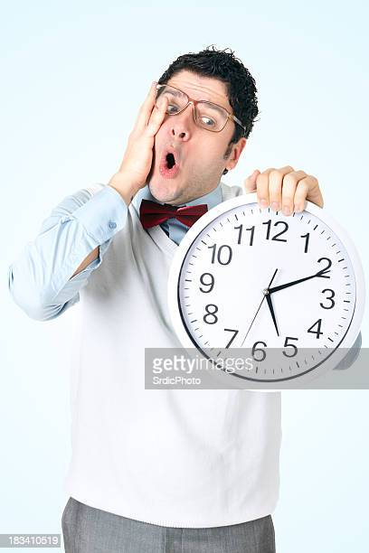 Surprised businessman with glass holding large clock