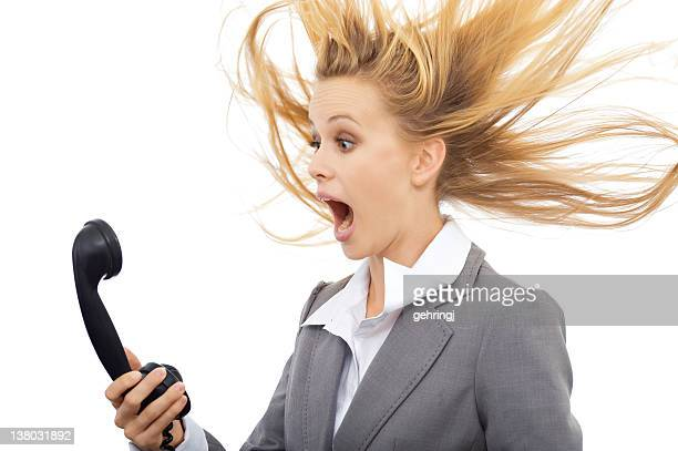 A surprised businesswoman holding a black telephone