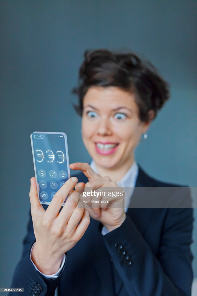 Surprised Businesswoman Using Futuristic Transparent Mobile With Euro Sign