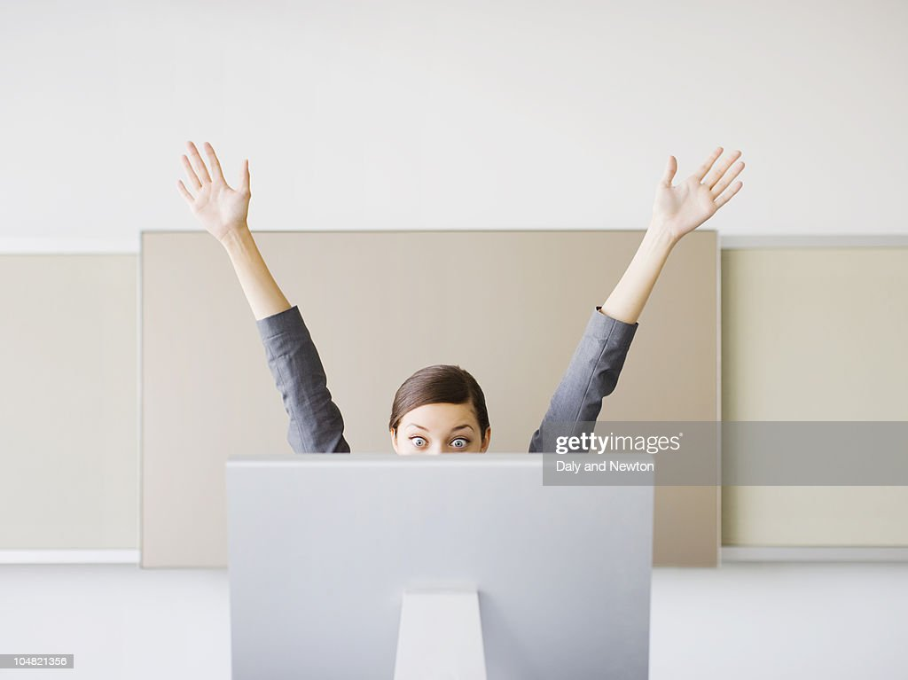 Surprised businesswoman with arms raised looking at computer : Stock Photo