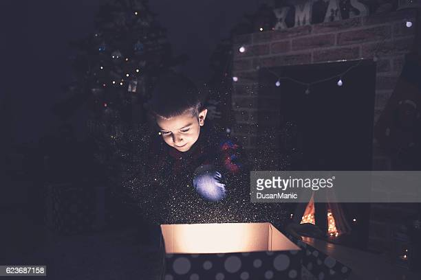 Surprised child opening and looking inside a magic gift