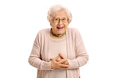 Surprised elderly woman looking at the camera and laughing isolated on white background