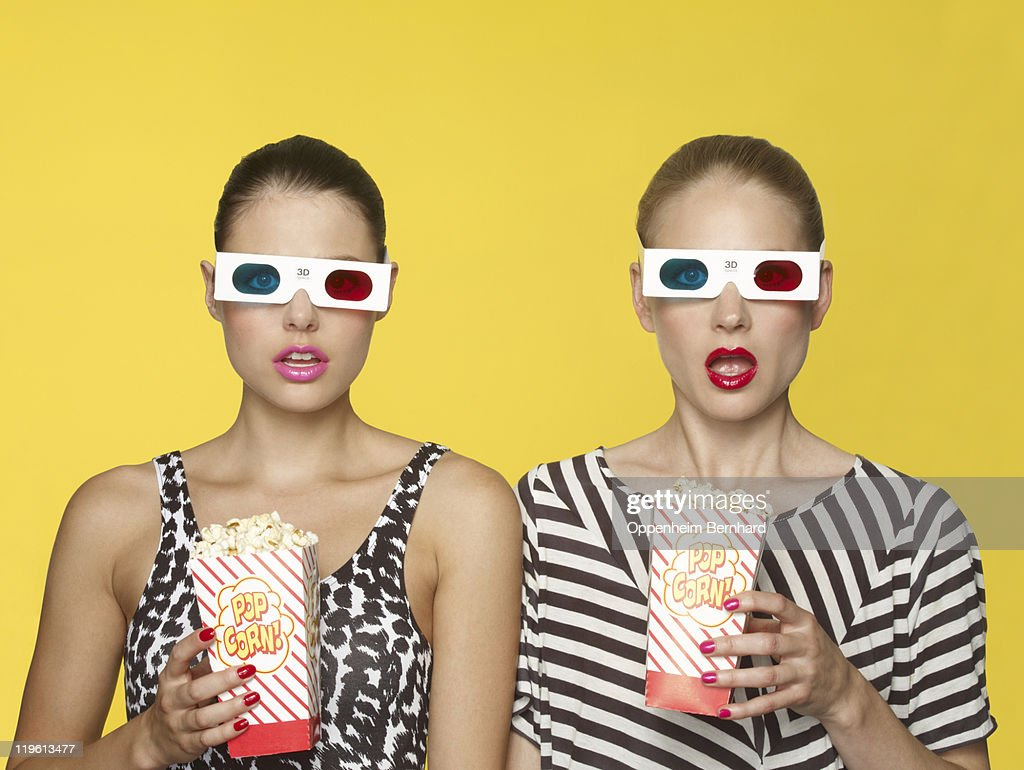 surprised girls watching 3D film with popcorn : Stock Photo