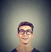 Surprised happy man wearing glasses looking up