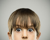 Close up portrait of surprised little boy with raised eyebrows. Horizontal shot of real kid on gray background. Photography from a DSLR camera. Sharp focus on eyes.