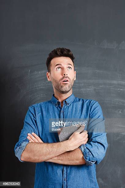 Surprised man against blackboard, holding a book in hands