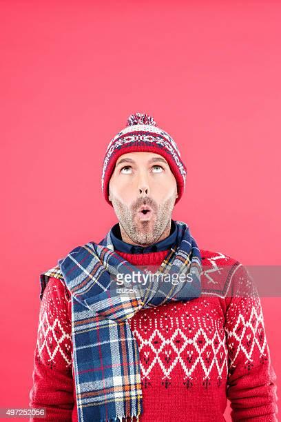Überrascht Mann im winter outfit mit Roter Hintergrund