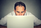 Surprised man with wide eyes hiding behind a laptop computer staring at the screen with a shocked scared face expression