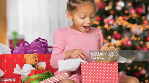 Surprised Mixed Race girl opening gift box on Christmas