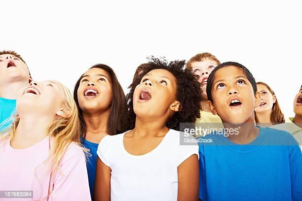 Surpris multi ethnique enfants regarder en l'air sur fond blanc