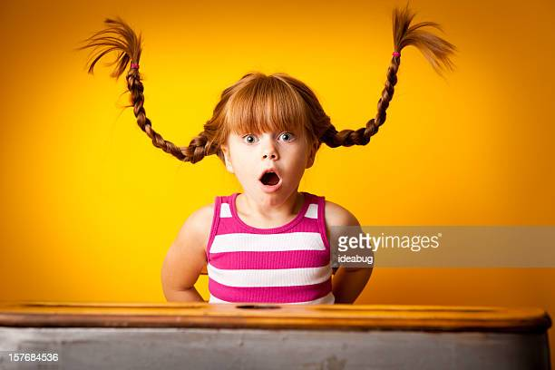 Surprised Red-Haired Girl with Upward Braids in School Desk