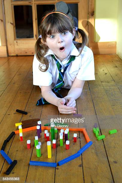 Surprised schoolgirl playing with bricks