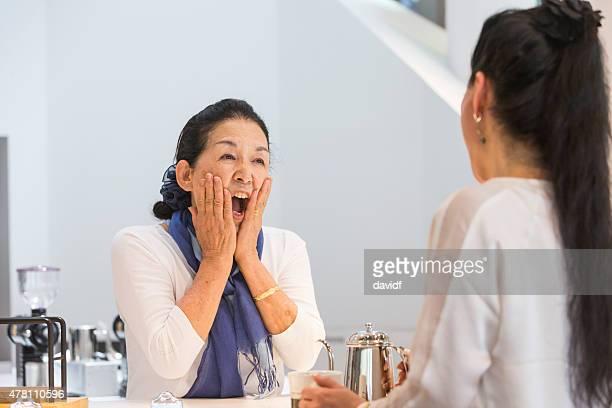 Senior mujer sorprendida japonés que sirve en el Café