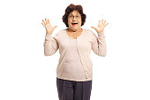 Surprised senior lady gesturing with her hands isolated on white background