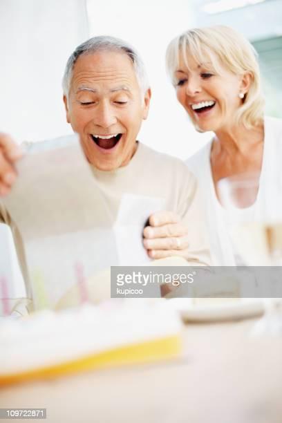 Surpris femme homme senior avec le Cadeau d'anniversaire d'ouverture