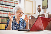 Surprised senior woman sitting in front of laptop at home.