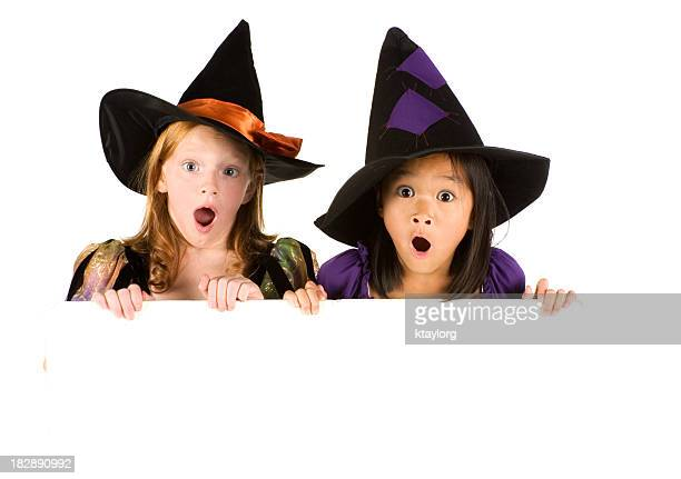 Surprised witches holding blank sign