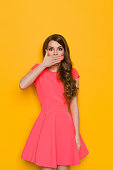 Surprised elegant young woman with curly long brown hair rising eyebrows and covers her mouth with hand. Three quarter length studio shot on yellow background.