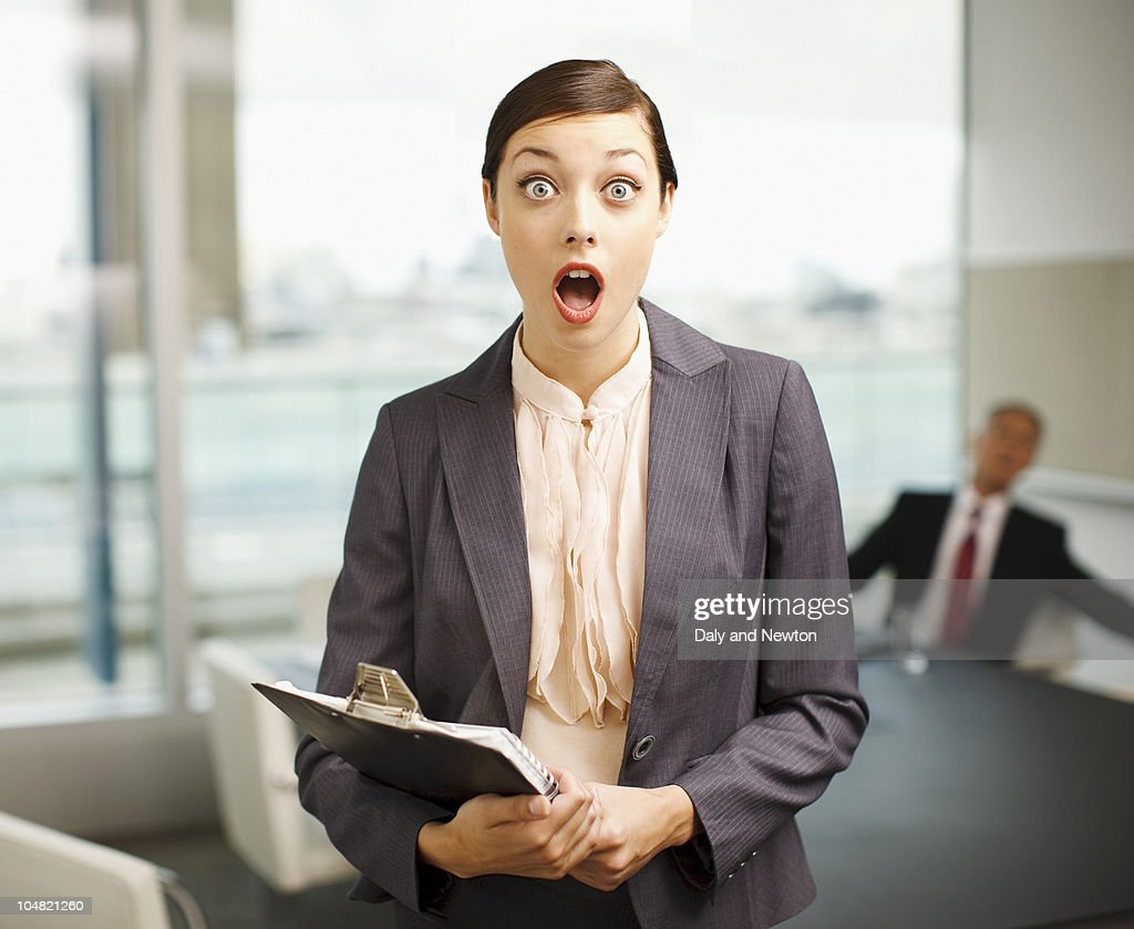 Surprised woman holding clipboard in conference room : Stock Photo