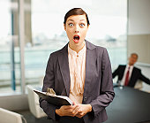 Surprised woman holding clipboard in conference room