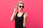 Blond short hair young woman in black round vintage sunglasses looking to right direction over pink color background. Stylish fashion portrait