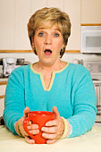 Surprised woman in kitchen holding coffee mug