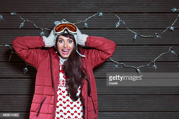 Surprised woman in winter outfit, wearing puffer jacket and goggle