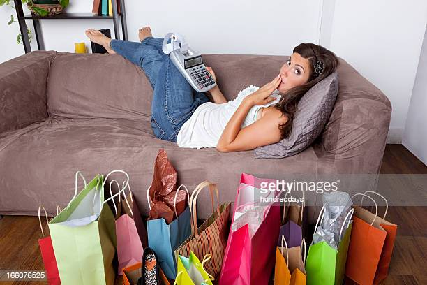 Surprised woman lying on couch with adding machine and shopping