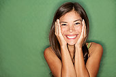 Surprised excited woman on green background. Cheerful multiracial Asian / Caucasian female model joyful. See more