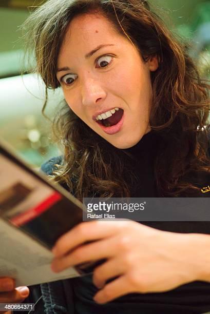 Surprised woman reading magazine