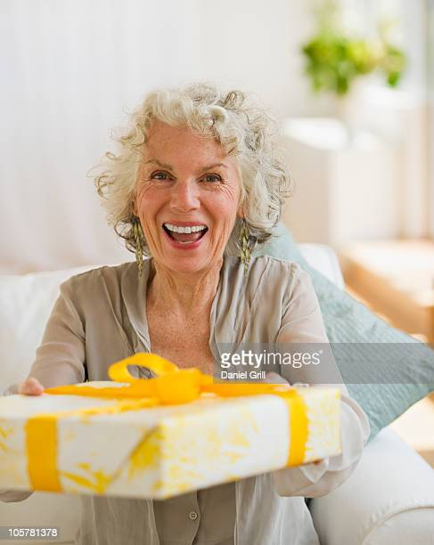 Surprised woman receiving a birthday gift