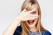 Surprised young blond woman peering though fingers
