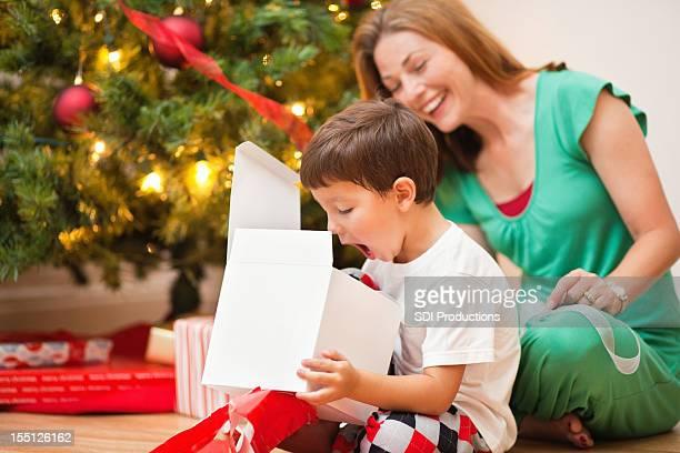Surpris jeune garçon ouverture Noël présente avec maman