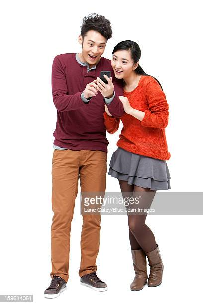 Surprised young couple with smart phone in Chinese New Year